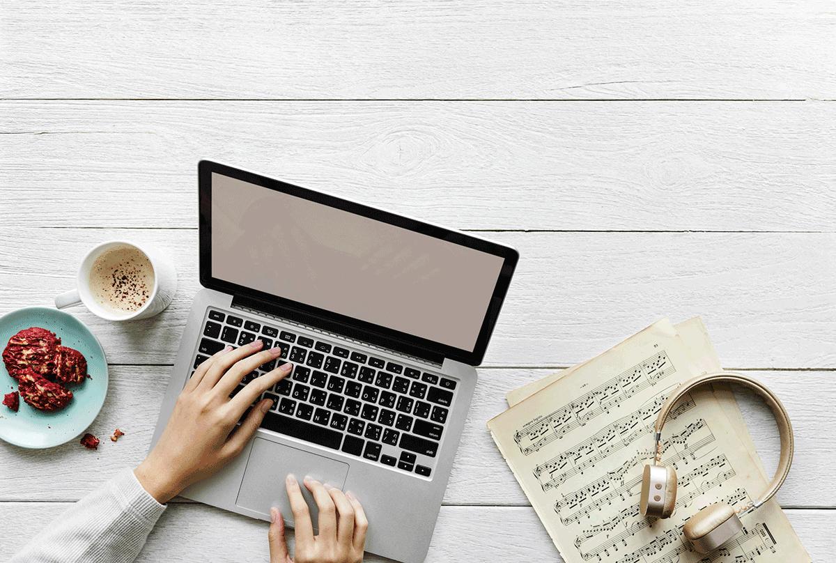 Laptop und Musiknoten am Arbeitsplatz