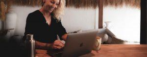 Texterin Sandra sitzt selbstbewusst bei der Arbeit vor dem Laptop